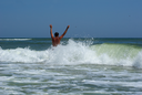 A man with his hands up his back to the camera on a background of a sea wave with spray foam. Young man bathing in the sea.