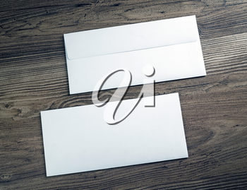 Two white blank envelopes on wooden background. Front and back side.