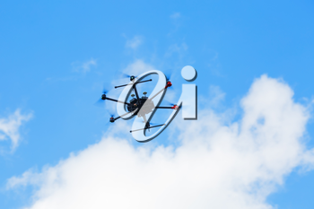 Flying hexacopter drone against a blue sky with clouds.