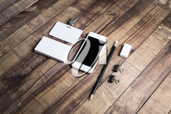 Smartphone with blank screen, business cards, badge, pencil, eraser and metal clamps on wood table. Blank stationery template.
