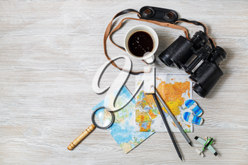 Travel plan background. Map, binoculars, magnifier, pencils, coffee cup, airplane and flip flops on light wooden background. Top view. Flat lay.