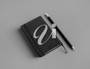 Blank black notepad and pencil on gray paper background. Template for branding design.