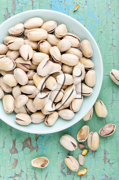 Pistachio nuts on wooden background, top view