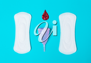 Pad, menstrual cup, with a drop of blood on a blue background. The view is flat. Concept of critical days, menstruation