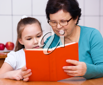 Grandmother is reading book with her granddaughter, indoors