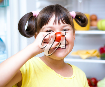 Happy girl eating tomatoes standing near refrigerator with fruits and vegetables