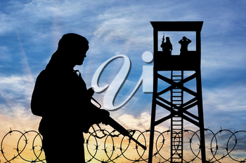 Concept of terrorism. Silhouette of a terrorist and the observation tower at sunsetr