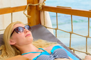 Young woman resting at beach in sunglasses. tourism and recreation concept