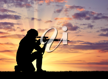 Silhouette of a terrorist with a weapon against a background of a sunset