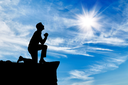 Silhouette of man praying at the top against the beautiful cloudy sky