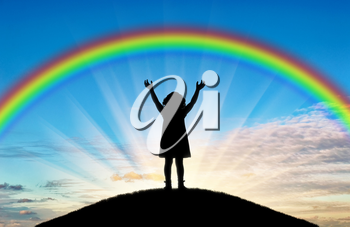 Silhouette of a happy little girl child with raised arms trying to touch the rainbow. A conceptual scene of a happy childhood