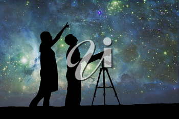 Silhouette of Telescope. Elements of this image furnished by NASA. The boy and girl are watching the night sky. Love under the stars