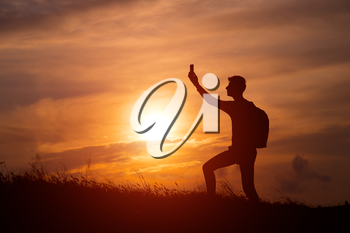 Silhouette of tourist man spread hand on top of a mountain enjoying sunset. Sport and active life concept. man taking photos of sunset with mobile phone