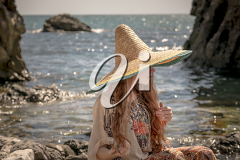 Beautiful boho styled model wearing white top and sombrero posing on the beach in sunlight