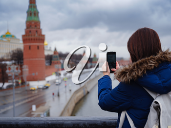 Young asian beautiful woman tourist taking pictures on mobile phone on the background of Moscow Kremlin, Russia