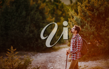 Young Man Traveler with backpack relaxing outdoor with rocky mountains on background. Lifestyle, and hobby concept