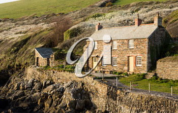 View of stone cottage and hillside in late evening sunlight in Port Quin, Cornwall, England, UK