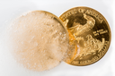Gold eagle one ounce coin emerging from a frozen ice block to illustrate concept of gold coming out of deep freeze and price going to rise