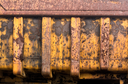 Detail of rust and remaining yellow paint on heavy yellow industrial truck and equipment abandoned in economic recession