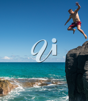 Dangerous leap into warm blue ocean off rocks at Lumahai Beach on Hawaiian island of Kauai
