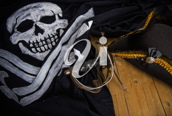 Classic pirate black felt captain's cocked hat and old sword lying on a wooden floor next to the Jolly Roger flag