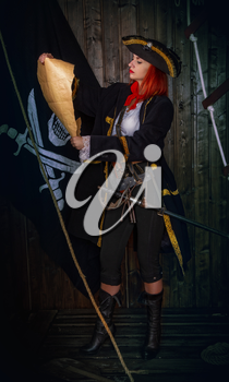 Young attractive armed girl pirate captain examines an old map on a background of the flag Jolly Roger