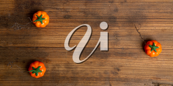 Three artificial pumpkins on a rough wooden background with place for your text. Top view.