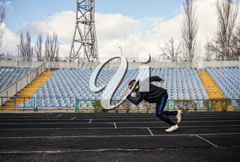 man in sportswear goes in for sports jogging through an empty stadium
