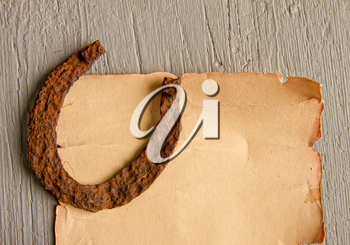 A very old rusty horse horseshoe a symbol of good luck lies on an empty paper scroll