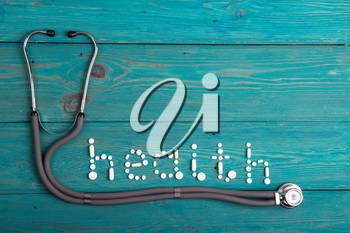 Health concept - pills, stethoscope on the wooden desk