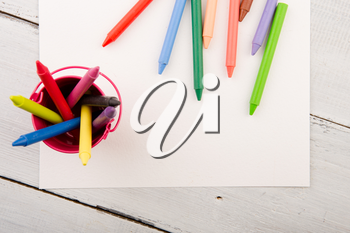 colorful crayons and blank paper on the wooden desk