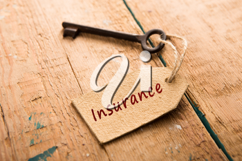 home insurance concept - old key with tag