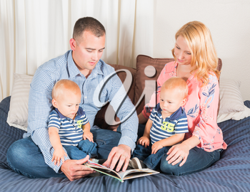 Young Hispanic Man With Blue Shirt and Young Caucasian Woman Wearing Pink Blouse Reading to Twin Baby Boys