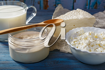 Curd, cheese and sour cream on blue wooden background