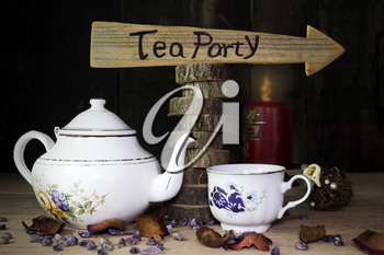 Tea Party. Cup of Tea and Teapot On Wooden Table With Arrow Sign in the Background