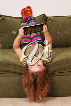 little girl lying upside down on bed and play with tablet