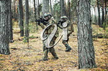 Pair of norwegian Rapid reaction special forces FSK soldiers in field uniforms in action in the forest