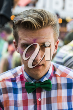 Lviv, Ukraine - August 30, 2015: Man with bow tie  watches festival of colors in a city park in Lviv.