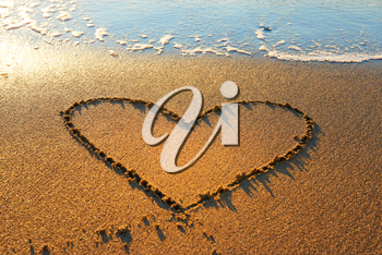 Heart drawn on the beach sand with sea foam and wave