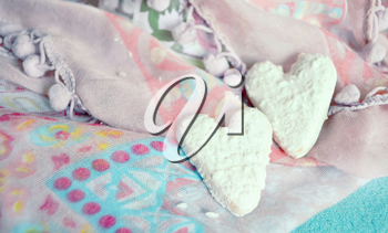 Cookies in the shape of hearts on the textiles background. Boho style. Love concept background. February 14 Holidays. Happy valentines day celebration.