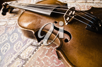 Still life with vintage violin. Closeup of old wooden violin. Stringed music instrument on abstract background.