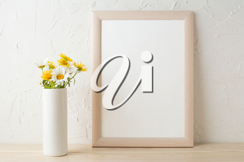 Frame mockup with white and yellow chamomiles in vase. Poster white frame mockup. Empty white frame mockup for presentation design.