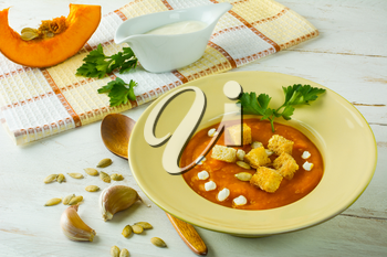 Roasted pumpkin squash vegetable soup with cream, pumpkin seeds, garlic croutons and parsley in a light yellow plate on white wooden background