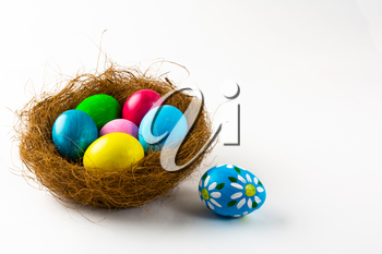 Multicolored Easter eggs in a nest and blue Easter egg with floral design on white background. Easter background. Easter symbol. Copy space