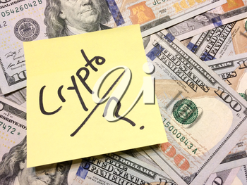 American cash money and yellow post it note with text Crypto with question mark in black color aerial view